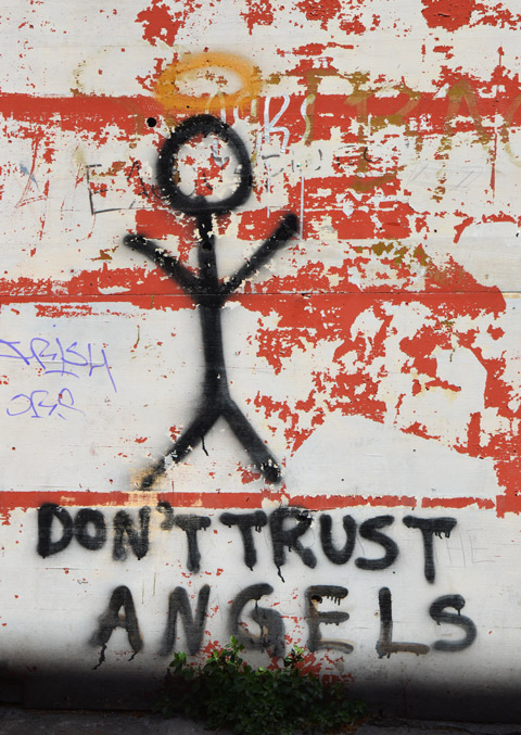 street art in Thessaloniki Greece - stick figure person with a yellow halo and the words underneath: Don't trust angels