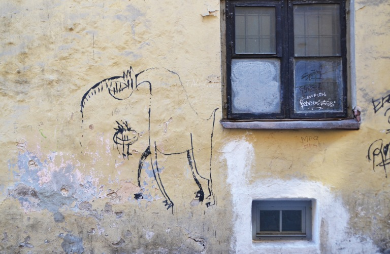 on a wall beside w window, two line drawings of animal creatures, on dinosaur like and the other a small round thing