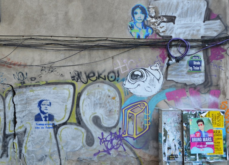 small pieces of graffiti on a wall, a paste up woman, a paste up fsh, a stencil head with words, also a poster for a Bruno Mars concert