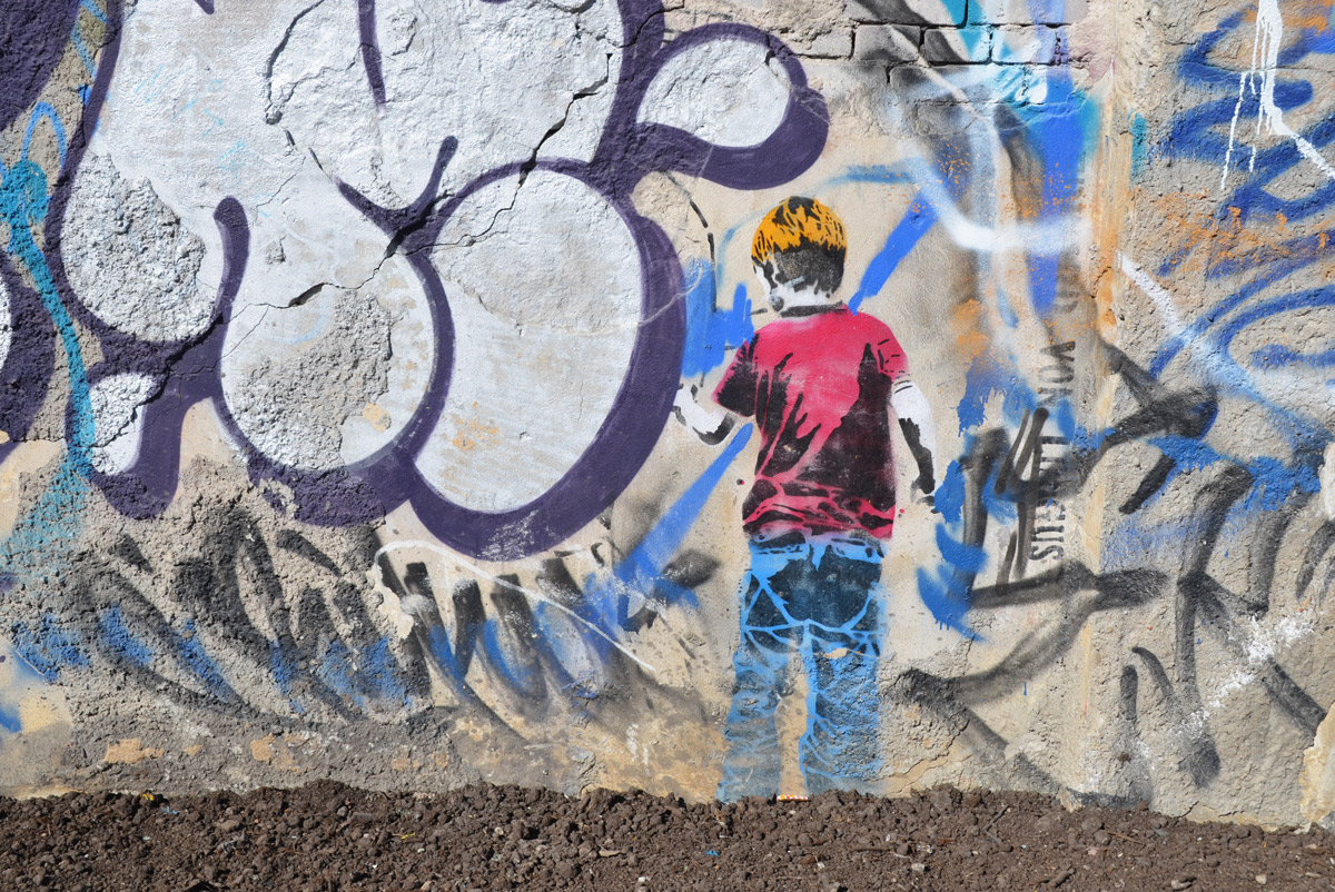 painting of a blond boy with a red T shirt and blue jeans is facing a wall and drawing on it.