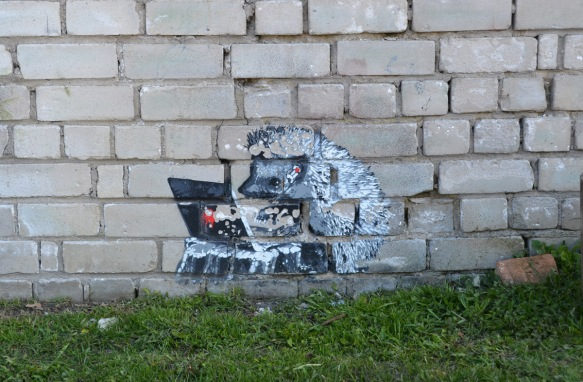 graffiti, a small grey and white hedgehog is working on a laptop