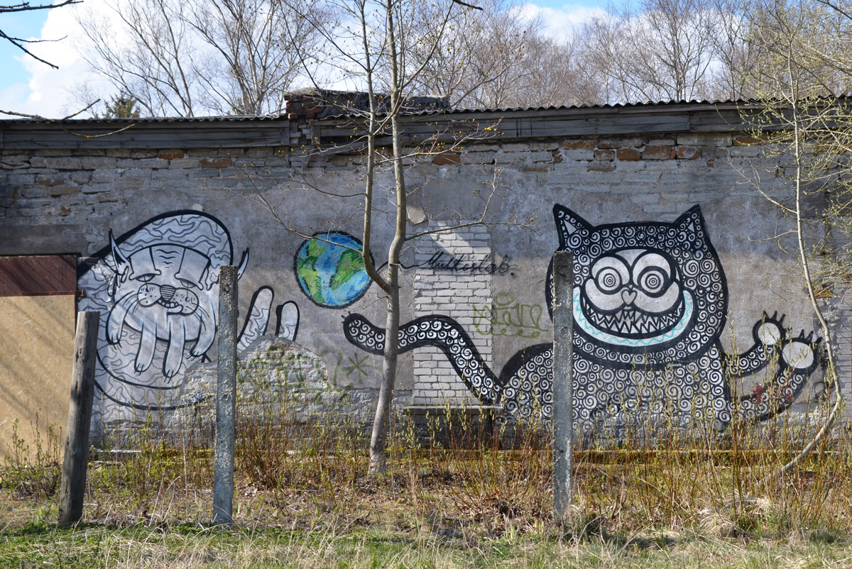 street art by multistab. A blue and green small plaet earth in between two large black and white creatures. One looks like a grinning cat, the other might be a cat but migh be something else