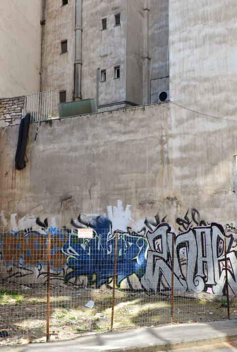 street art in Thessaloniki Greece - at ground level on the side of a concrete building, behind a chain link fence, two text tags