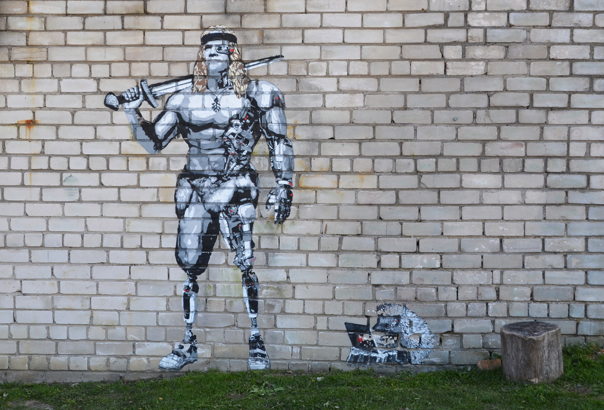 a large muscular partially clad man with a weapon over his shoulder, on a grey brick wall, a small hedgehog is working on a laptop beside him. graffiti