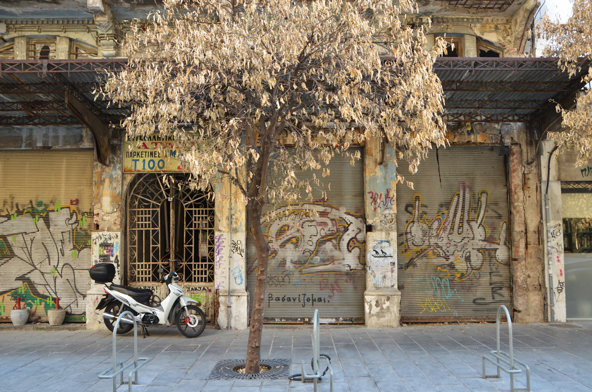 street art in Thessaloniki Greece - a motorcycle and a tree in front of a bulding, the metal screens covering the windows have street art on them