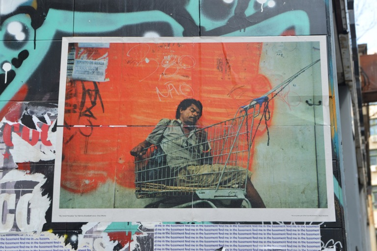 poster on a wall outdoors, of a man sleeping in a shopping cart outside.