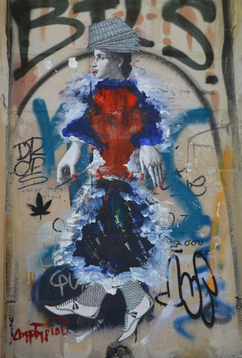 a black and white paste up of woman that has been painted over with many colours except for the head, hands and feet (wearing old fashioned shoes), on a wall in Athens,