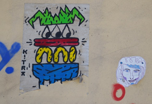 cartoonish character with angular green hair, three eyes, then a red layer, a yellow layer and on the bottom a blue layer, it seems to be looking at a little paste up of a head