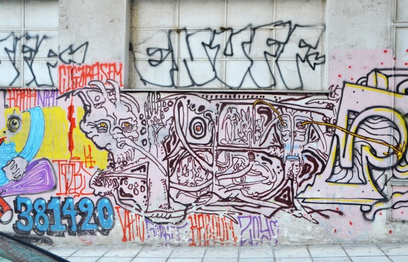 street art in Thessaloniki Greece - elaborate line drawing on a concrete wall, abstract, with a face in it.
