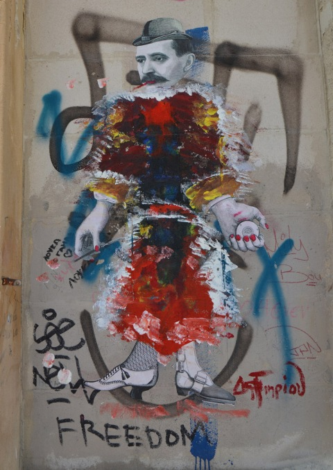 a black and white paste up of woman that has been painted over with many colours except for the head, hands and feet (wearing old fashioned shoes)