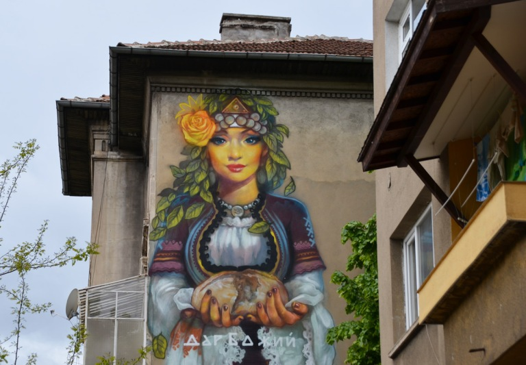 top part of mural by massimo, woman's upper body and head. she is holding a loaf of bread in her hands.