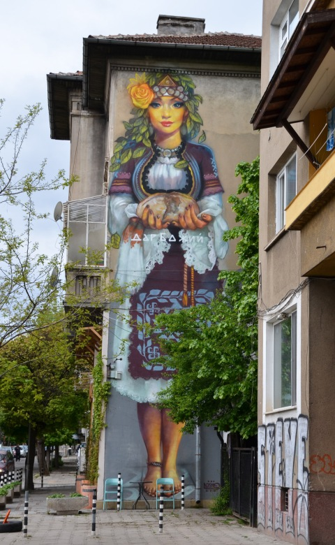 mural by street artist massimo on the side of a building in Sofia, mural is about 3 storeys high. Woman is dressed intraditional Bulgarian costume