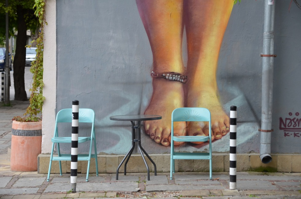 two turquoise metal chairs and a little round grey table sit on a sidewalk in front of a large mural of a woman. Only the feet, ankles and calfs are visible.