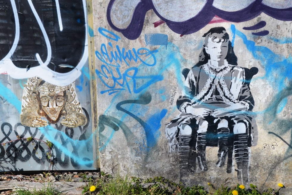 street art by MinaJaLydia on a concrete wall, two pieces, a pasteup of an elaborate abstract drawing of a face and hands as well as mushrooms and other plant life. the other is a young person sitting on a chair, with 4 legs hanging from the chair.