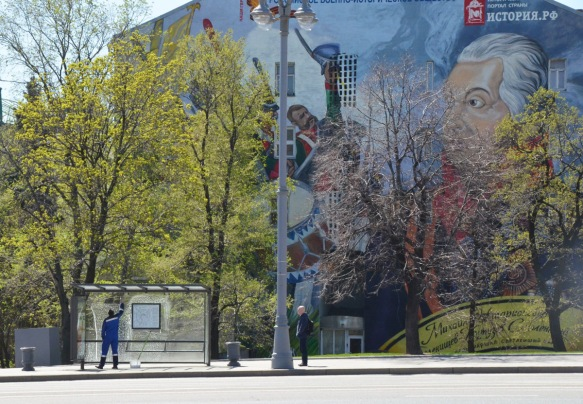 behind a tree, a large mural with soldiers and drummers in uniform