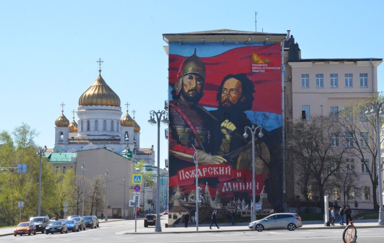 historical theme mural on a wall in Moscow, church with gold domes in the background