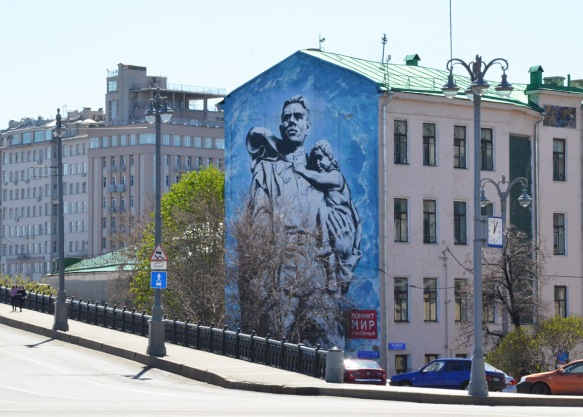 large mural, blue background, man with child on his back looking over his shoulder