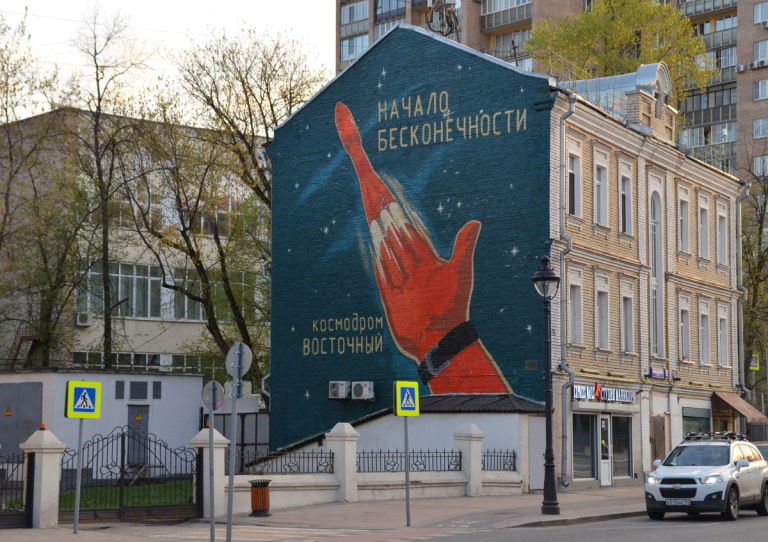 on the side of abuilding, a large mural about Russian cosmonauts, a rocket coming off a red hand into a dark teak blue sky, with Russian words