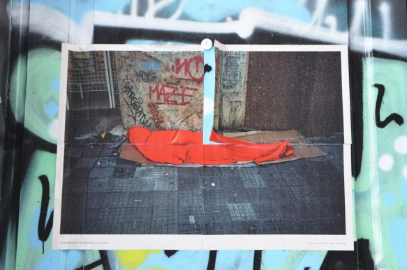 poster on an outdoor wall, a person wrapped in a red blanket and lying on the sidewalk
