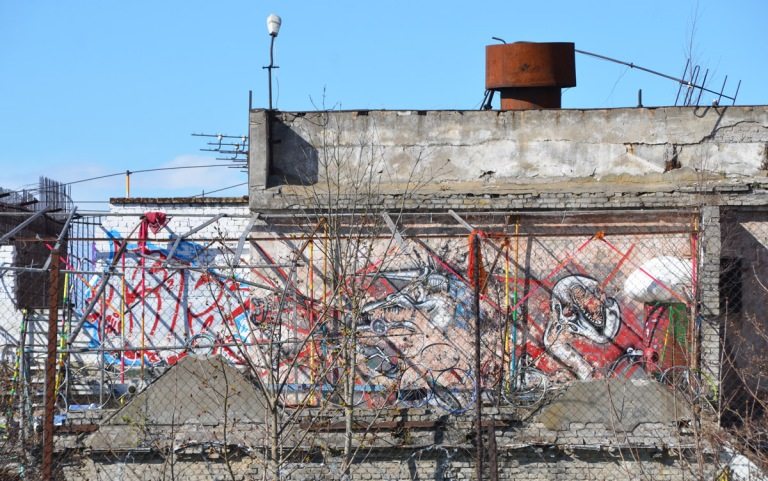 street art on a wall that is hard to see because it is behind a fence