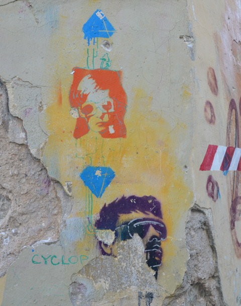 three stencils on a wall, an orange womans face, a blue diamond and a purple man with sunglasses on