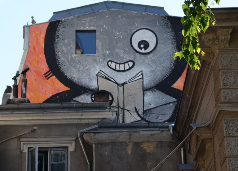 large mural of a grey face reading a book. One of the eyes is actually a window