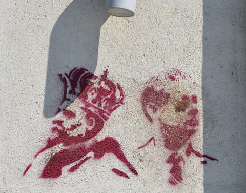 two red stencils of men's heads, one is a king wearing a crown and one is a man wearing a tie. the latter is dirty, looks like it has mud in his eye
