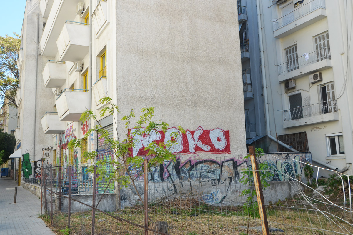 street art in Thessaloniki Greece - two text graffiti pieces on the side of an apartment building, the top one is roko and is white lettering on red background.