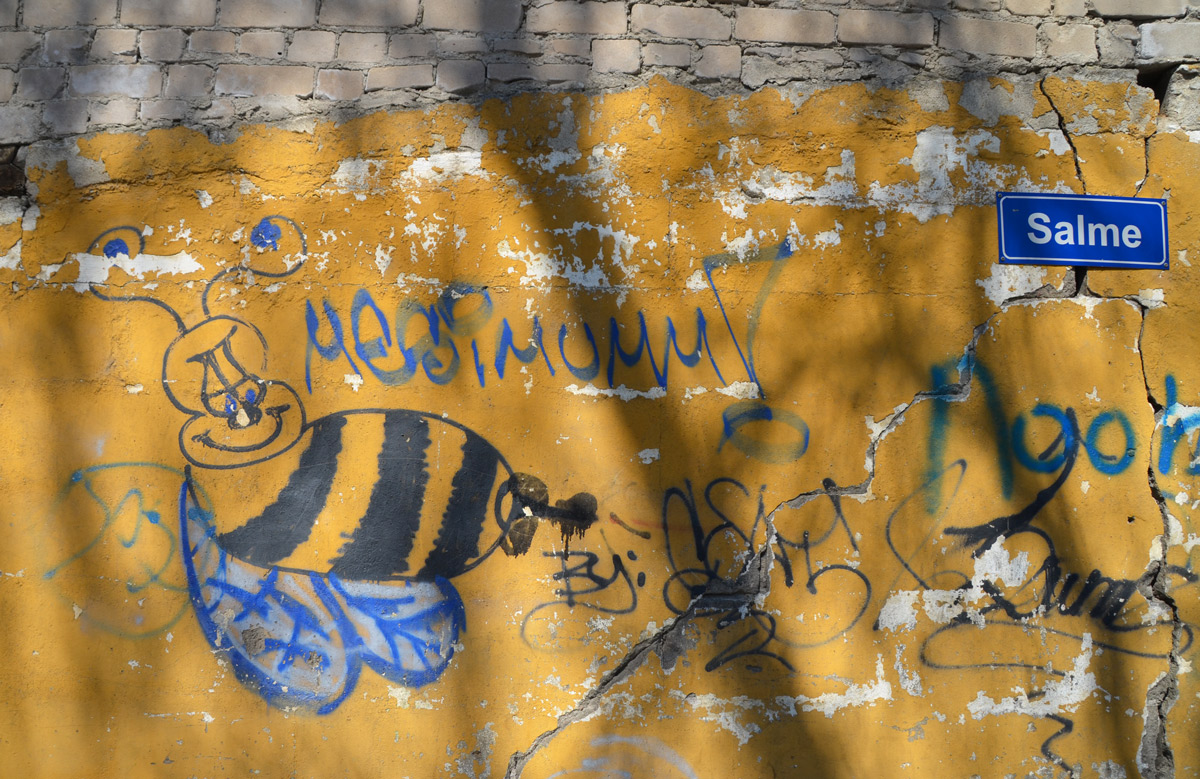 a big bee on a yellow wall, street sign that says Salme