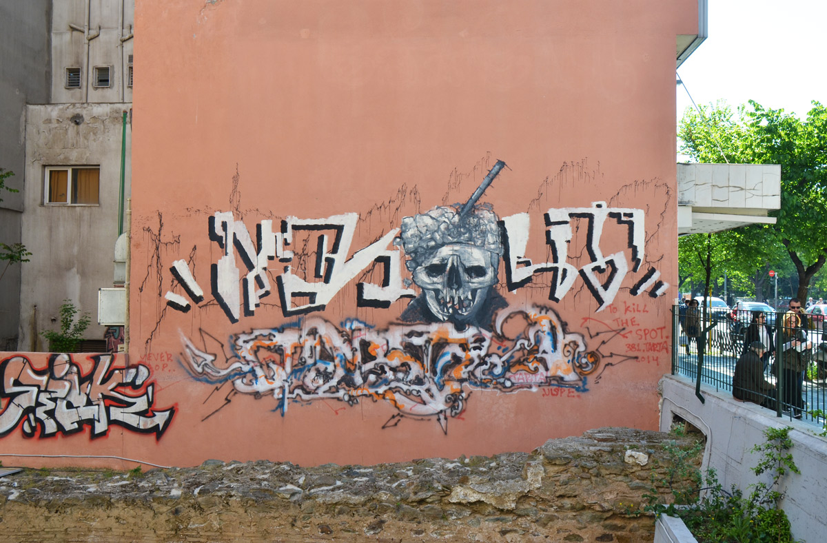 street art in Thessaloniki Greece - a skull in the middle of a text graffiti , on a pink wall