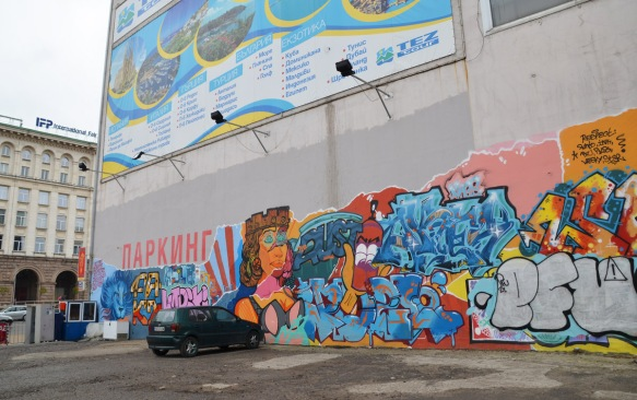 long mural on a wall, Soifa, about Sofia, lion nead and head of Sofia looking regal
