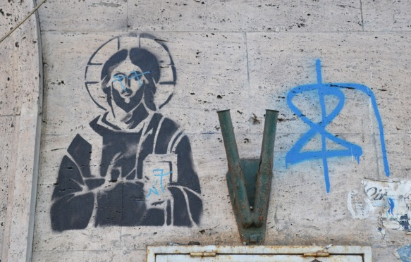 black stencil of Jesus, with halo around his head, a book in one hand, the other hand is pointing the book