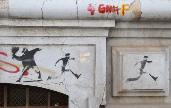three stencils in a row, on the left a man throwing something, the next two are men running away
