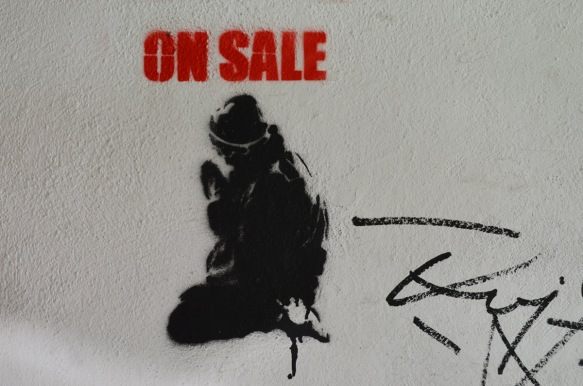 stencil, black, seated person with red block capital letters above the head that say on sale