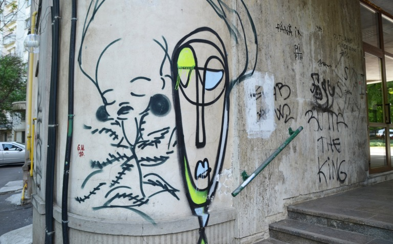 two line drawn graffiti faces on a concrete wall