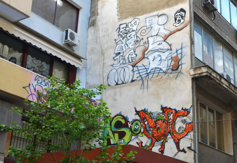 street art in Thessaloniki Greece - two pieces, on top is a black and white abstract drawing and below is a yellow and orange throw up
