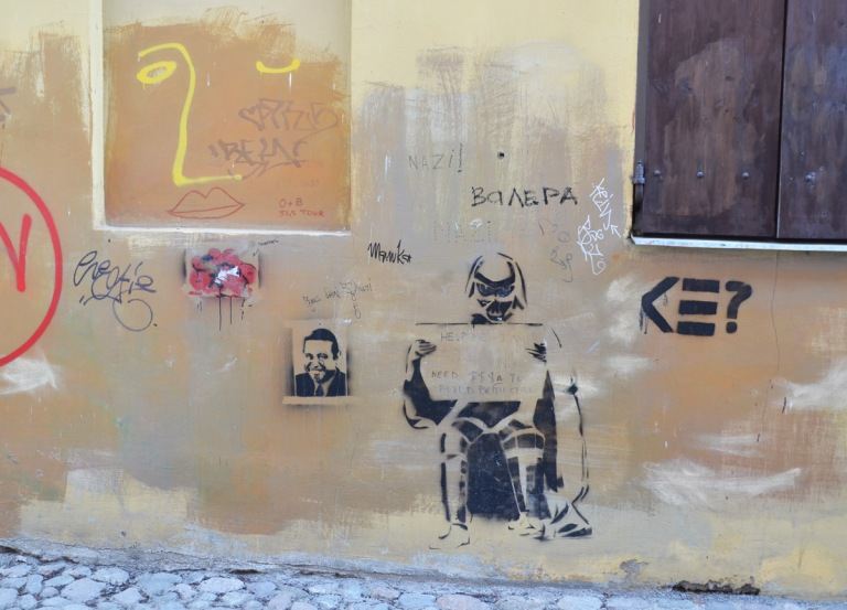 a few small piece of graffiti, a yellow face, a black stencil of a man's head and shoulders, a stencil of Darth Vader, and some scribbles,