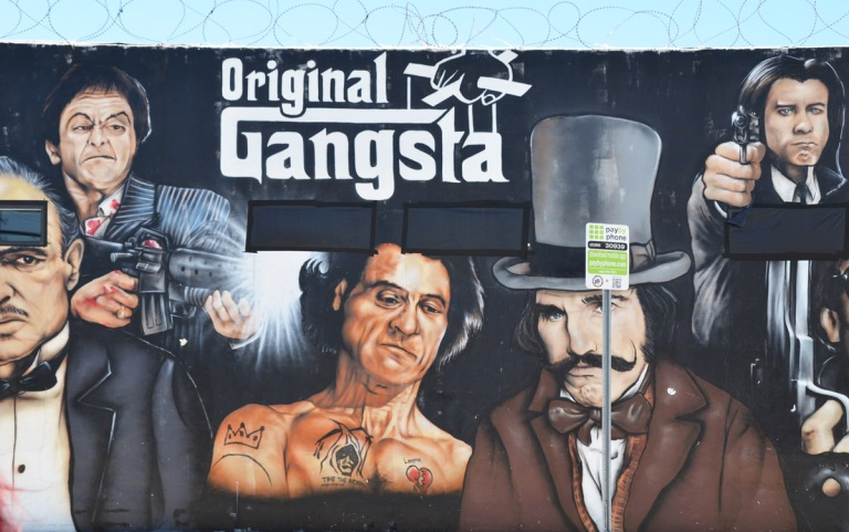 mural with images of famous actors in movie roles, Al Pacino in Scarfacce, a man in a tophat, a man with a machine gun
