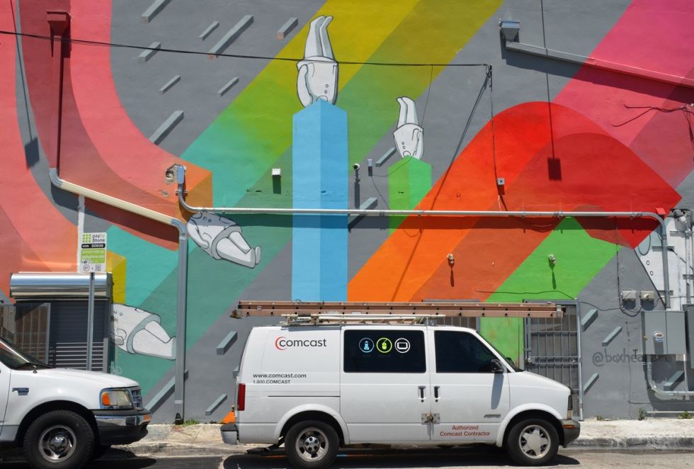 a white COmcast van is parked in front of a building that has been painted with a mural by boxheadarts, of white figures with their heads in various square tubes in different colours running in different directions