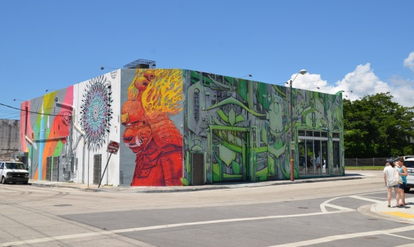 a building on a corner with murals on all sides