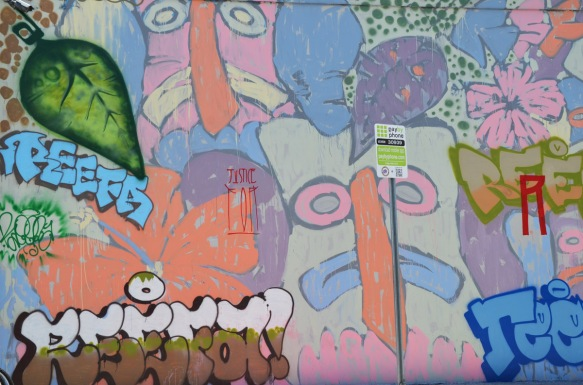 stylized faces in pastel colours, at the edges of a tribute mural to reefa, painted by a number of different artists