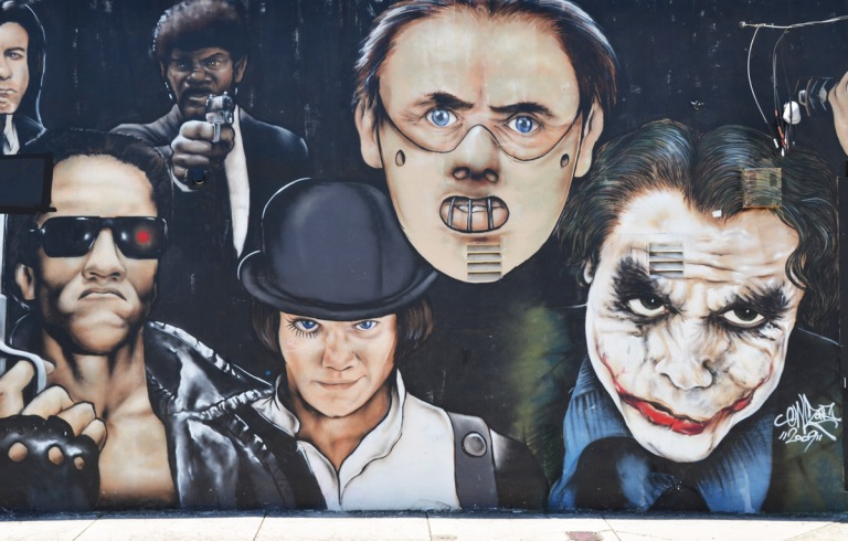 Clockwork Orange, masked Anthony Hopkins and Heath Ledger as the Joker, faces in a mural on a wall, black background, Wynwood