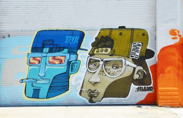 two stylized heads painted on a door, one is in blue tones and the other in olive green tones, the left is dmjc crew and the right is saile_one. both have cigarettes and baseball caps on backwards. also wearing glasses.