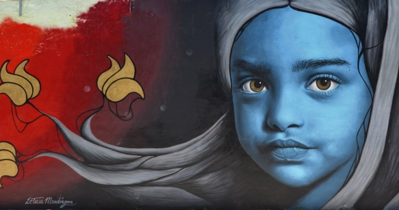 mural by Leticia Mandragora of a girl with a blue face and a long head scarf in grey that trails to the left, along with three flowers
