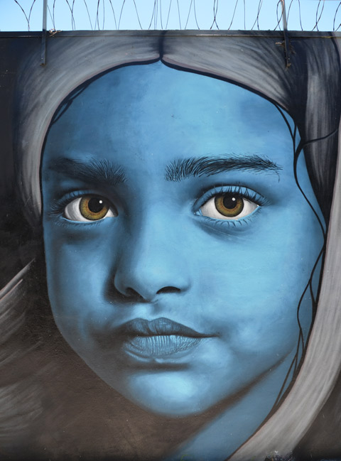 close up a large girl's face painted blue in a large mural, greenish eyes, head scarf on her head