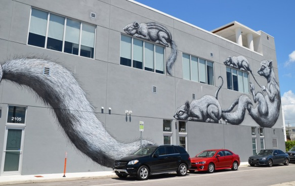three cars parked in front of a large black and white mural on a grey building, by ROA, two adult animals and two babies
