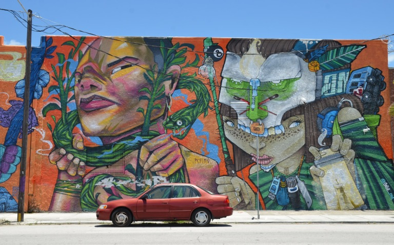 large mural by pesimo93, dmjc crew and saile_one - part of the mural with a red car parked in front of it.