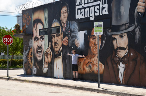 a young man poses in front a mural with images of actor's faces, original gangsta is the title of the mural, gangstawall