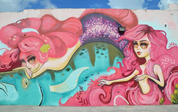 part of a larger mural by Tati Suarez, @tatunga, of mermaids - mermaids with long pink hair and purple fins swimming in blue water