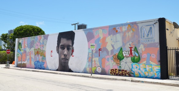 long horizontal mural by Axel Void with a young man's head inside a white circle in the middle, the edges are faces in pastel colours, stylized
